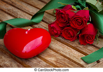 roses with red heart candle on wooden table