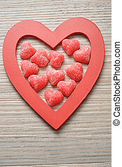 Valentine's Day. Wooden heart filled with sugar heart shape candy.
