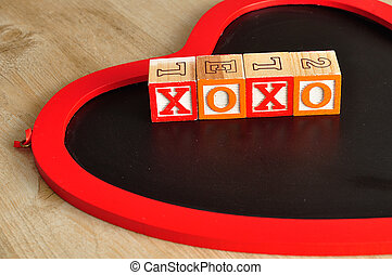 Valentine's Day. XOXO Spelled with colorful alphabet blocks and a chalk board in the shape of a red heart