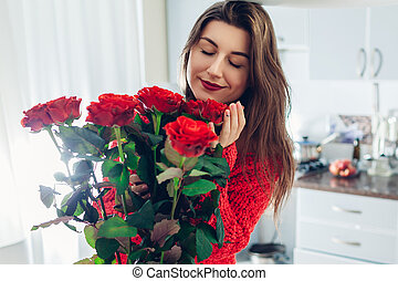 Valentines day. Young woman found bouquet of red roses on kitchen. Happy girl holding and smelling flowers.