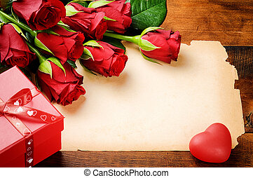 Valentine's frame with red roses and vintage paper on wooden table