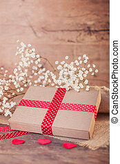 Valentine's gift with red ribbon on wood