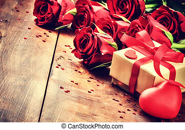 Valentine's setting with bouquet of red roses and present in...