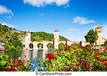 Valentre bridge in Cahor over red flowers, France