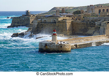 VALLETTA, MALTA - DEC 31st, 2019: View from Fort St Elmo on to the Ricasoli Grand Harbour East Breakwater and red lighthouse during strong waves