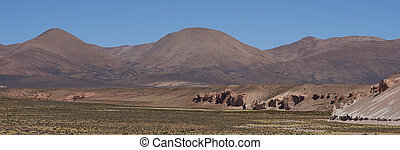 Valley on the Altiplano - Eroded cliffs along the wide...