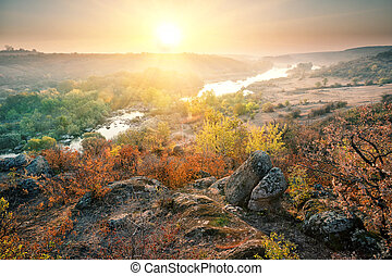 Valley with mountain river in the rocky shores at sunset