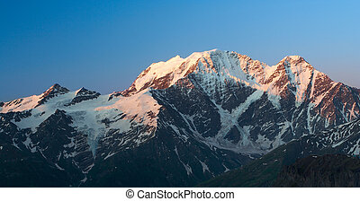 valley with snowed mountains at the sunrise time
