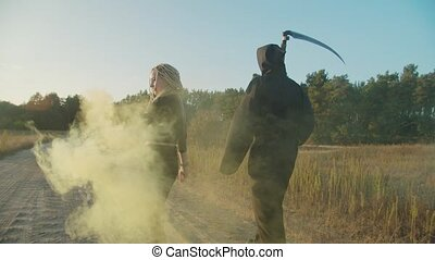 Rear view of creepy woman vampire and death reaper wit scythe walking in clouds of smoke on rural road in nature at twilight. Portrait of bloodthirsty vampire and grim reaper standing in autumn nature.