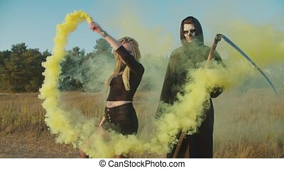 Scary female vampire with dreadlocks holding yellow smoke bomb and spooky grim reaper with scythe standing in clouds of smoke in nature at sunset while walking on rural road, haunting for victim.