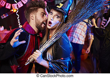 Vampire and witch at Halloween party