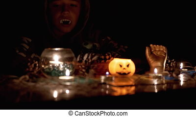 Vampire Boy with in Hood Sitting and Plays by Candle in Dark Room on Halloween. Silhouette of Boy. Creepy, dark mysterious night ambiance. Concept of children's party. Decorations with a pumpkin. 4K.