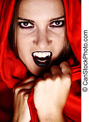 Vampire in red - Woman vampire showing her fang and covered...