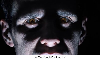 Vampire looks at the camera in the dark