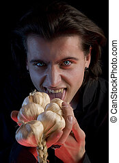 Vampire with scary eyes is licking garlic