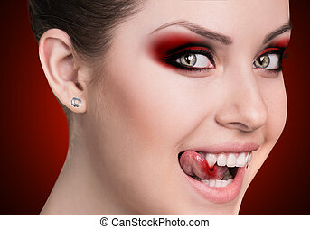 Mysterious vampire woman with fangs on the red background