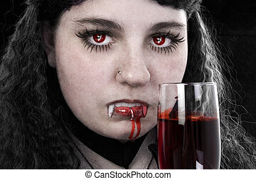 Vampiress with glass of fresh blood. Reflection of ghostly...