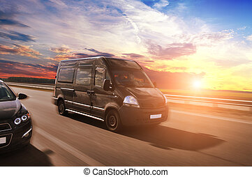 Van and car driving fast on the countryside road against blue sky with sunset