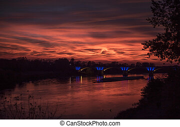 Van Gogh sky at sunset over Ticino river in Pavia, northern Italy