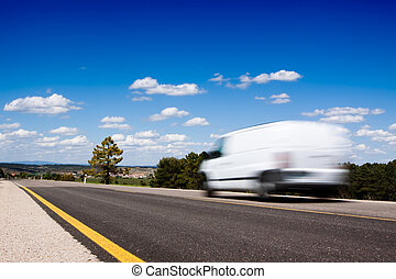 White van in a country road with some trees and a great blue sky above