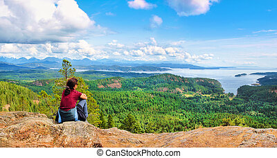Vancouver Island, BC, Canada - Woman sitting on a rock and...