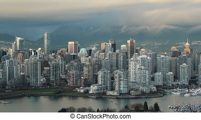 View of downtown Vancouver. Looking north with False Creek in foreground and mountains in the distance.