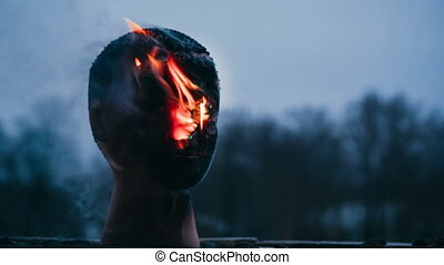 Vandal sets fire to the head of the dummy. Closeup video.