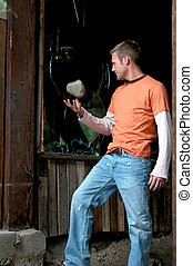 Vandal - A young man about to toss another rock through a...