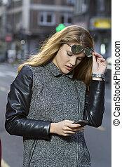 vandrande, smartphone, gata, ung kvinna