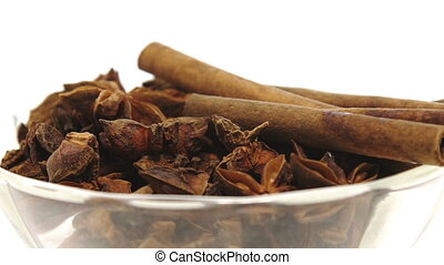 Vanilla and cloves in galss plate on white background -...
