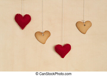 Vanilla cookies hanging over beige background - heart shaped...