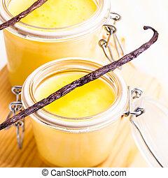 Vanilla custard in little jars on the table, sweet dessert