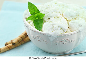 Vanilla ice cream with a sprig of fresh mint and chocolate pirouettes.