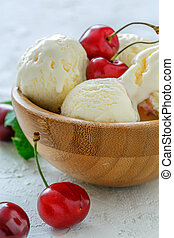 Vanilla ice cream with sweet cherry in a wooden bowl.