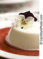 Vanilla panna cotta with berry sauce and spring flower