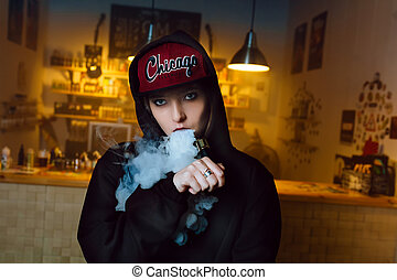 Vaping girl. Young hipster woman vape e-cig at the vapeshop....