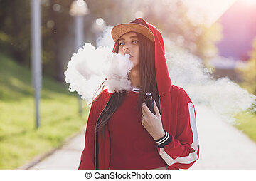 Vaping girl. Young woman vape e-cig. Pretty young female in black hat, red clothing vape ecig, vaping device at the sunset. Toned image. Hip-hop style.