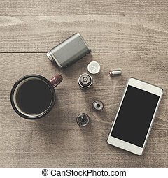 Vaping set, smartphone and coffee on the wood table.