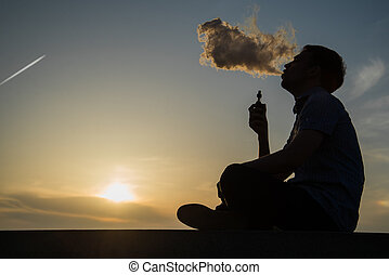 vaping young man with, produces vapor on sunset sky...