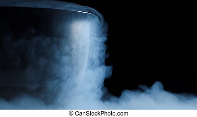 Vapor from liquid nitrogen from metal bowl creeps along flat...