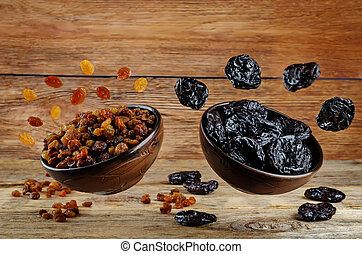 Variation of dried fruits: prunes and raisins on a dark wood...