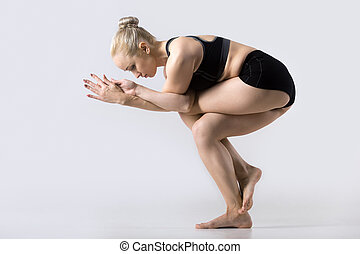 Sporty beautiful young woman practicing yoga, doing Eagle Fold Pose, variation of Garudasana, exercise for ankles, calves, thighs, hips and shoulders, working out wearing black sportswear, studio