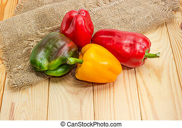 Varicolored bell peppers on the wooden rustic table