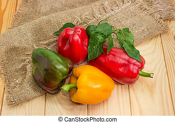 Varicolored bell peppers with leaves on the wooden rustic table