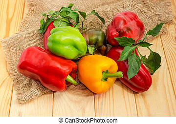 Varicolored bell peppers with twigs and leaves on wooden surface