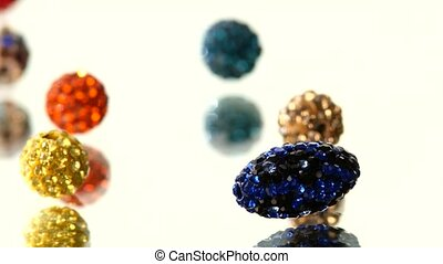 Shiny, different colorful beads isolated on white background, cam moves to the left, rotation, close up