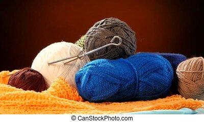 Varicolored yarn balls with spokes on orange scarf, brown...
