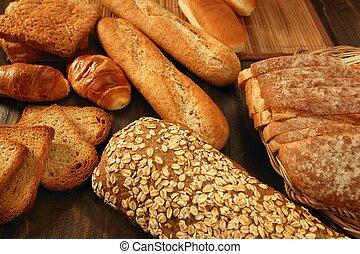 Varied bread still life over dark wood background