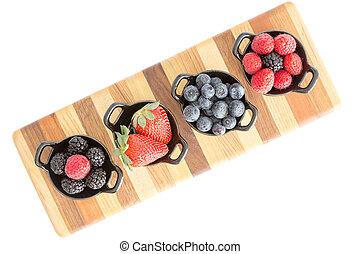 Varieties of fresh berries in individual dishes