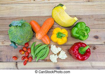 Variety fresh vegetable on wooden background.
